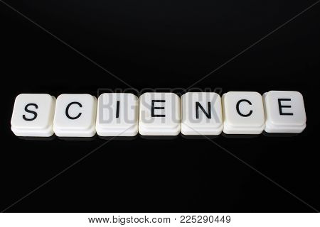 Science text word title caption label cover backdrop background. Alphabet letter toy blocks on black reflective background. White alphabetical letters..