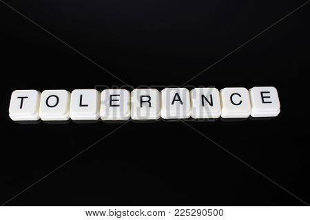 Tolerance text word title caption label cover backdrop background. Alphabet letter toy blocks on black reflective background. White alphabetical letters..