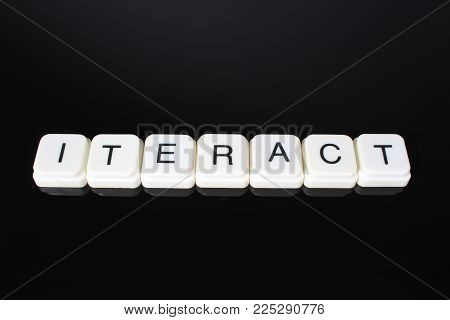 Interact text word title caption label cover backdrop background. Alphabet letter toy blocks on black reflective background. White alphabetical letters..