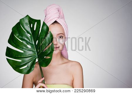 a dazed woman with a towel on her head after the shower put patches under her eyes