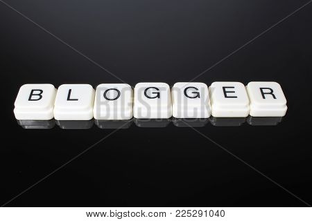 Blogger text word title caption label cover backdrop background. Alphabet letter toy blocks on black reflective background. White alphabetical letters. Blogger.