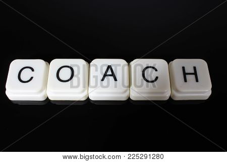 Coach text word title caption label cover backdrop background. Alphabet letter toy blocks on black reflective background. White alphabetical letters..