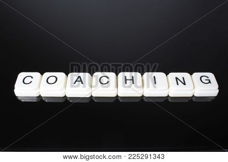 Coaching text word title caption label cover backdrop background. Alphabet letter toy blocks on black reflective background. White alphabetical letters..