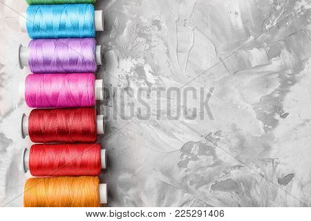 Colorful sewing threads on grey background