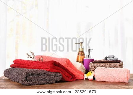 Set of fresh towels and toiletries on wooden table against light background
