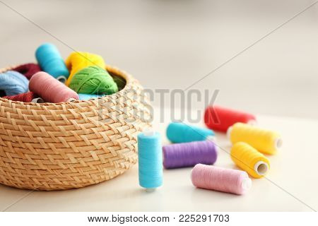 Wicker box with color sewing threads and crocheting clews on table