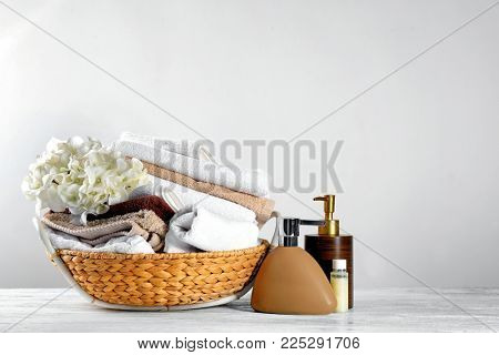 Wicker basket with set of fresh towels and toiletries on wooden table against light background