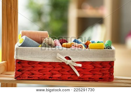 Wicker box with color sewing threads and crocheting clews on shelf indoors