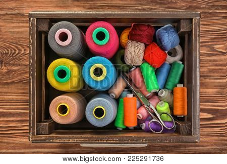 Wooden box with color sewing threads and crocheting clews on table, top view