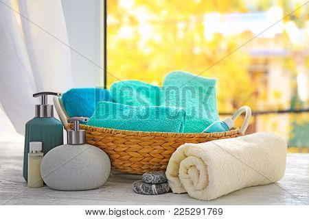 Wicker basket with set of fresh towels and toiletries on wooden table near window