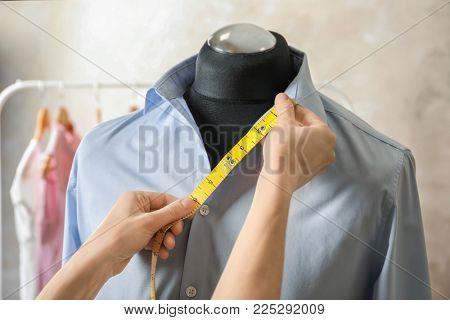 Tailor measuring part of shirt on mannequin in workshop