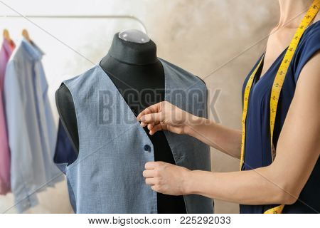 Seamstress tailoring vest on mannequin in workshop