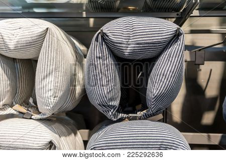 Neck pillows hanging on metal bar in store display for sale