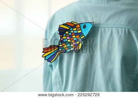 Paper fish on man's back, closeup. April fool's day prank