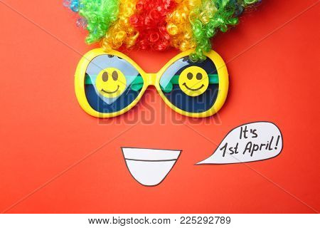 Funny glasses and rainbow wig on color background. April fool's day composition