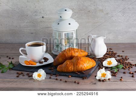 Fresh french buttery croissants for breakfast with a cup of aroma coffee and candlestick lamp. Good start for day.