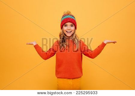 Happy Young girl in sweater and hat shrugs her shoulders while looking at the camera over orange background