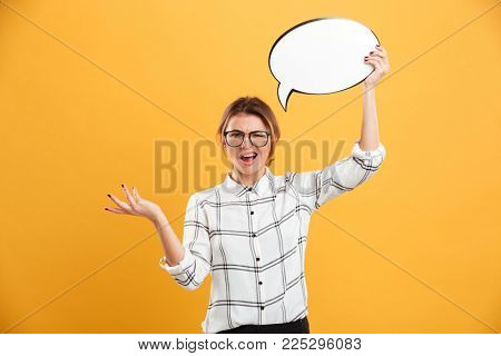 Portrait of indignant woman 20s wearing eyeglasses holding blank speech bubble and throwing hand aside isolated over yellow background