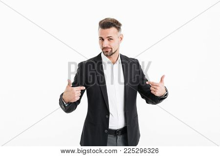 Portrait of a smiling mature businessman dressed in suit pointing fingers at himself isolated over white background