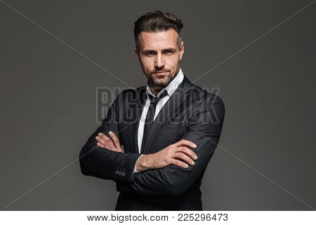 Portrait of an attractive mature businessman dressed in suit pointing finger at camera isolated over gray background