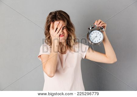 Displeased woman in t-shirt covering her face while holding alarm clock over grey background