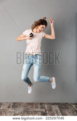Full length image of Joyful woman in t-shirt listening music from smartphone with earphones and jumping while having fun and showing peace gesture over grey background