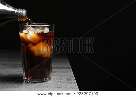 Pouring cola from bottle into glass with ice on table against black background
