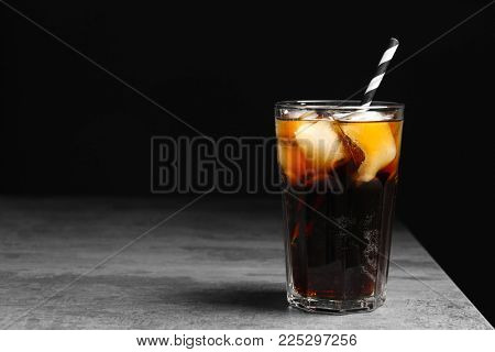 Glass of refreshing cola with ice on table against black background