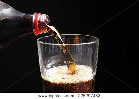 Pouring cola from bottle into glass on black background, closeup