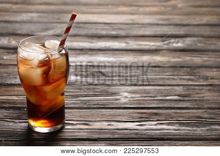 Glass of refreshing cola with ice on wooden background
