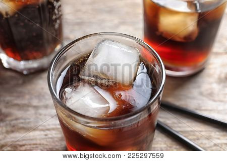 Glass of refreshing cola with ice on wooden table, closeup