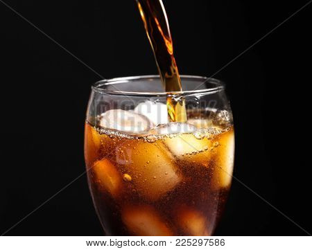 Pouring cola into glass with ice against black background, closeup