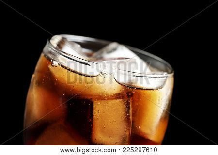 Glass of refreshing cola with ice on black background, closeup