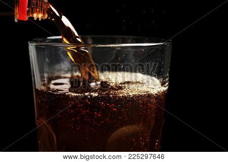 Pouring cola from bottle into glass against black background, closeup