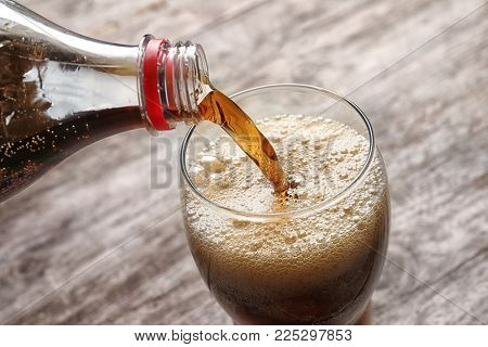 Pouring cola from bottle into glass on wooden background, closeup