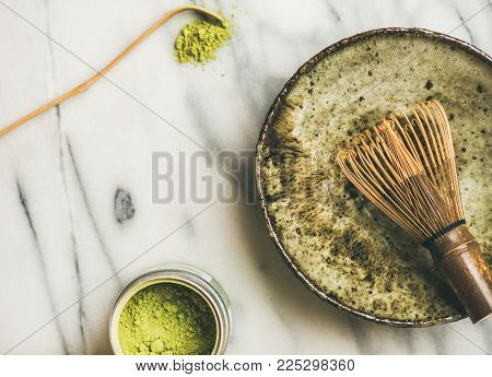 Flat-lay of Japanese tools for brewing matcha tea. Matcha powder in tin can, Chashaku spoon, Chasen bamboo whisk, Chawan bowl, cups for ceremony, grey background, top view, copy space