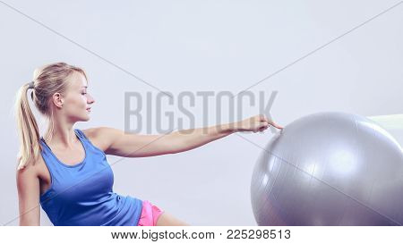 Sport, training, gym and lifestyle concept. Young attractive slim woman in sportswear doing fitness exercises with fit ball at home