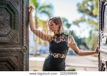 Backlit Blonde Woman In Black Lace Dress Opening Doors To Reveal The City.  Shot On February 4, 2018