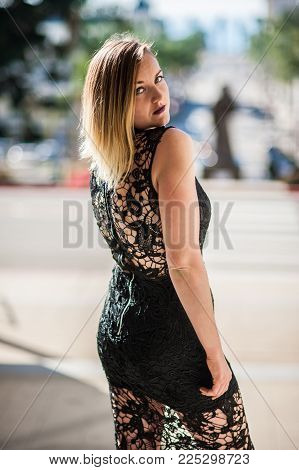 Black Lace Evening Gown On Beautiful Blond Woman Overlooking City Downtown Street While Looking Over