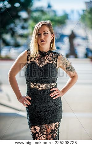 Elegant Woman In Black Lace Gown Standing With Hands On Hips Over City Downtown On Bright And Sunny