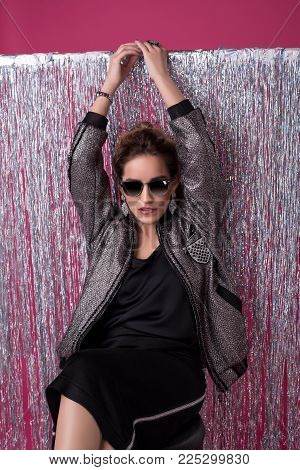Beautiful young girl in sunglasses wearing a black skirt, sexy top and a fashionable jacket sitting on a barstool cropped shot against silver background