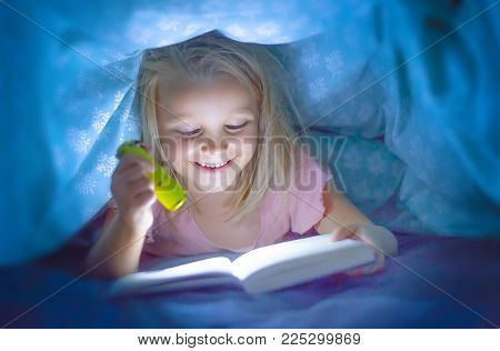 sweet beautiful and pretty little blond child girl 6 to 8 years old lying under bed covers reading book in the dark with torch flashlight smiling happy hidden covered by sheets excited at night
