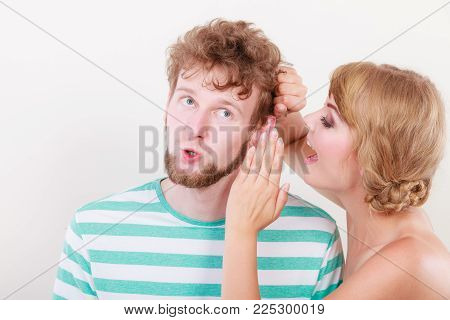 Closeup woman telling an astonished surprised man some secrets, couple talking