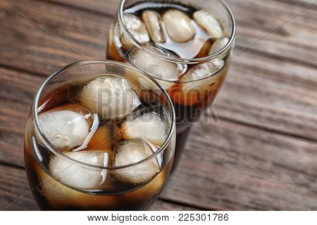 Two glasses of refreshing cola with ice on wooden table, closeup