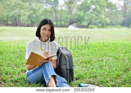 Education Concepts. Asian women reading books in the park. Beautiful women are relaxing in the park. Beautiful women are happy to read.  Asian girls love to study. Education of Asian Women.