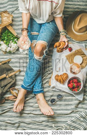French style romantic picnic setting. Woman in denim pants sits with glass of rose wine, strawberries, croissants, brie cheese, hat, sunglasses, peony flowers, top view. Outdoor gathering concept