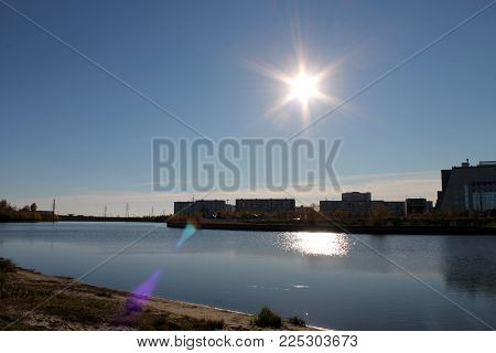 the sun shines, stand at home, the river runs, water, day,  clear clear sky, river bank, buildings.