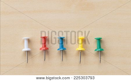 Colorful pin put on wooden table top background