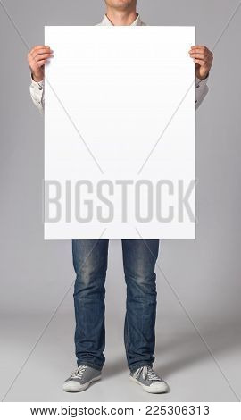 Photo. Man holding a blank poster. Template for branding identity. For graphic designers presentations and portfolios.