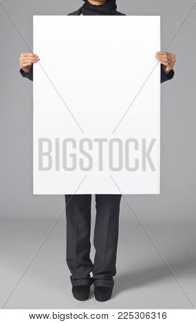 Photo. Woman holding a blank poster. Template for branding identity. For graphic designers presentations and portfolios.